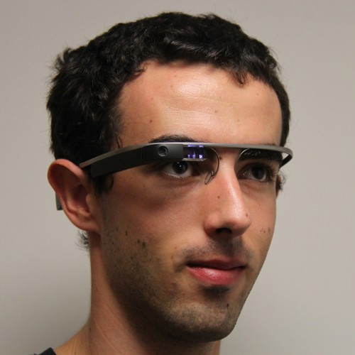 Shows me wearing Google Glass, with the screen illuminated.
